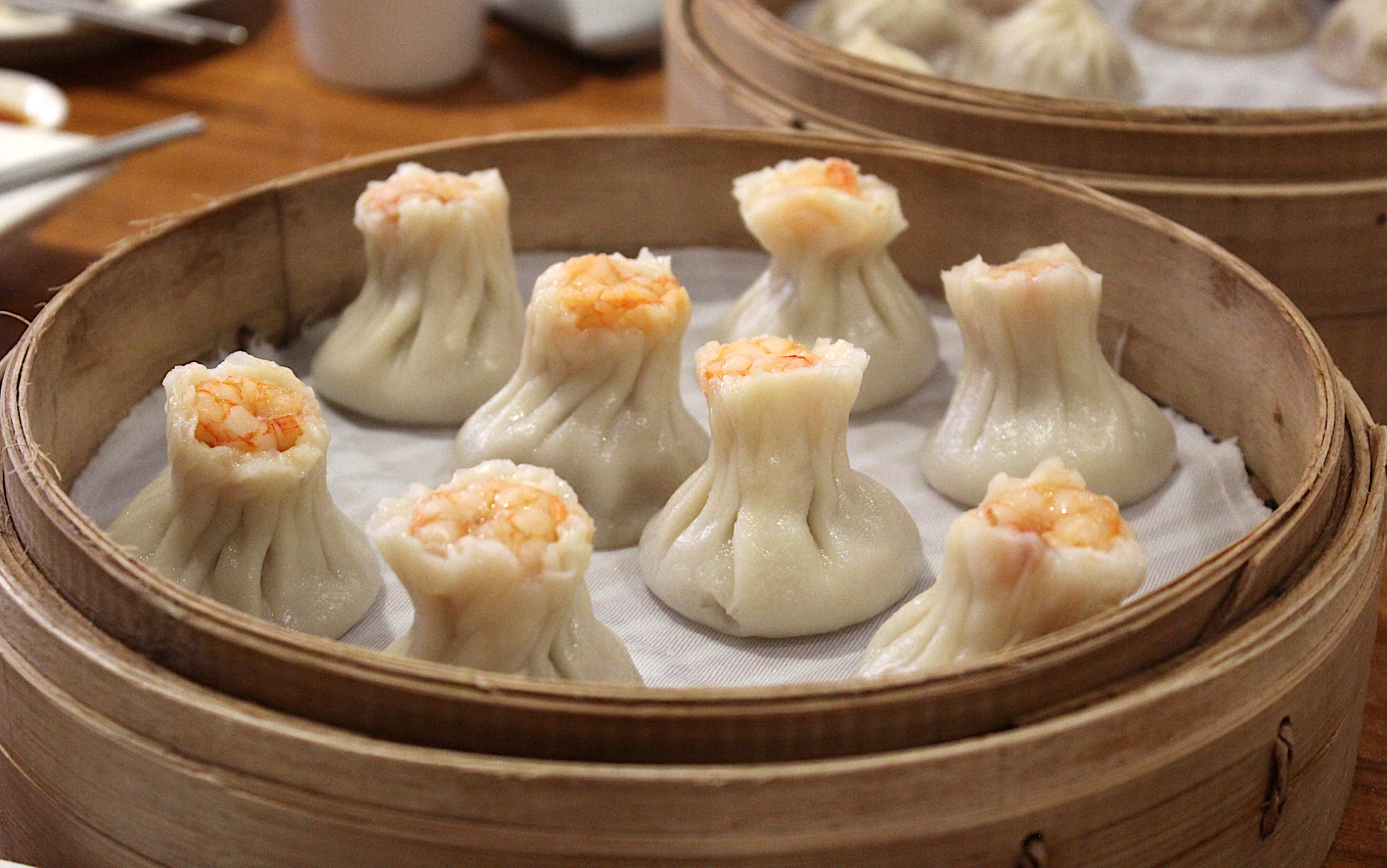 "xiaolongbao, or ""soup dumplings,"" served in steaming hot bamboo baskets."